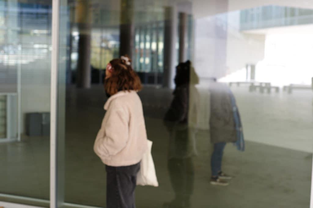 Zwei Personen in einer Spiegelung im Unipark Salzburg