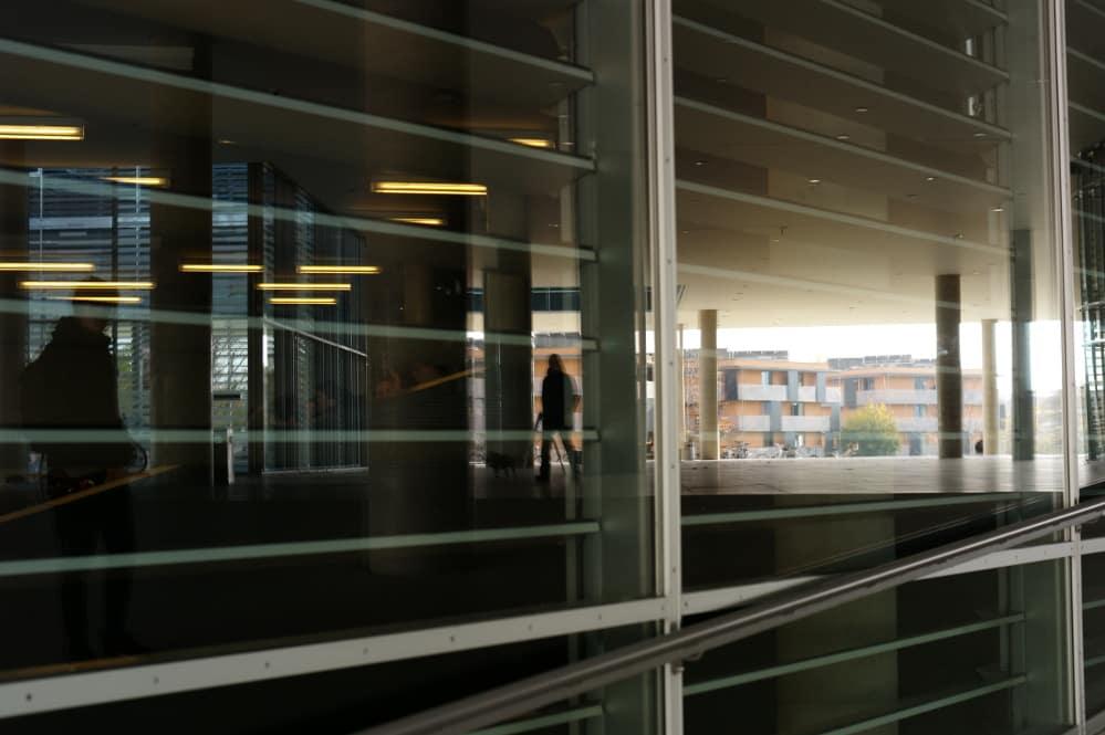 Person hinter einer Scheibe im Unipark Salzburg